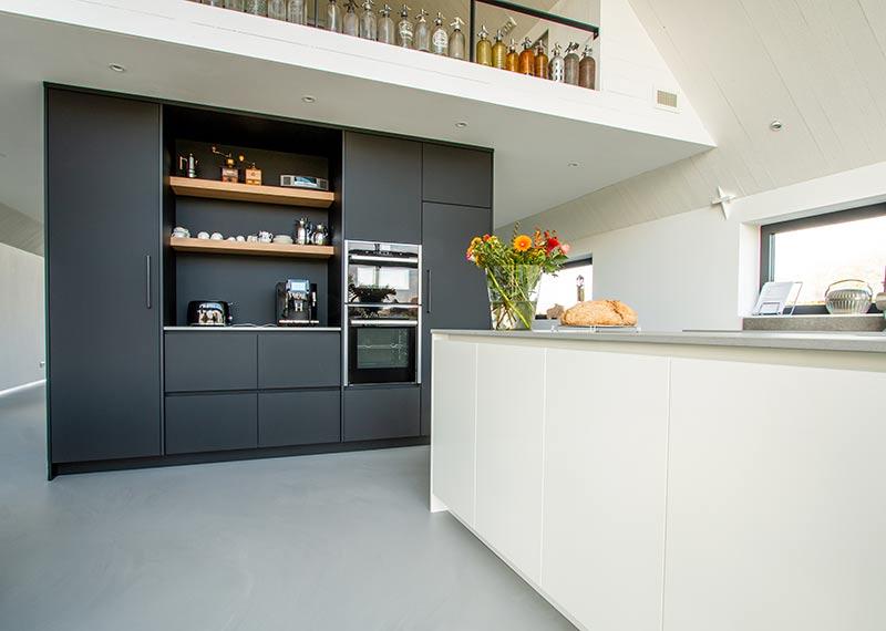 witte woonkeuken met zwarte kastenwand